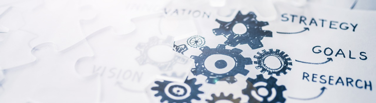 closeup of a sketch of a group of gears in blue ink with arrows pointing out to the words strategy, goals, and research